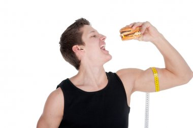 man with hamburger and tape measure around biceps over white background.