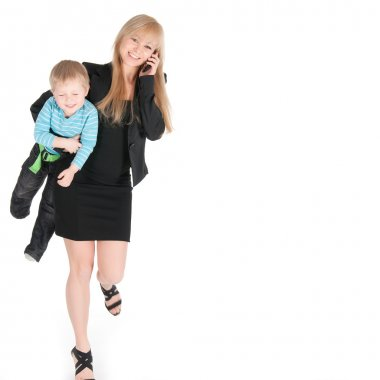 Young business woman speaking by phone and carrying her son under arm over white background