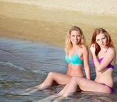 Dvě krásné mladé ženy, sedící ve vodě na pláži