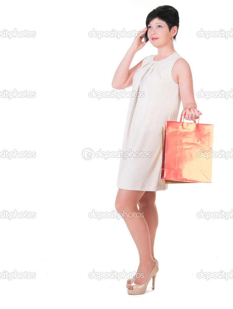 9d4abe5d0c0 Femme brune en robe crème avec des sacs à provisions posant– images de  stock libres de droits