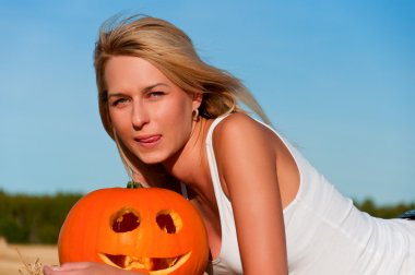 woman in jeans shorts posing on a bale with pumpkin