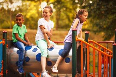 Caucasian girls and Afro American boy, on playground in kindergarten