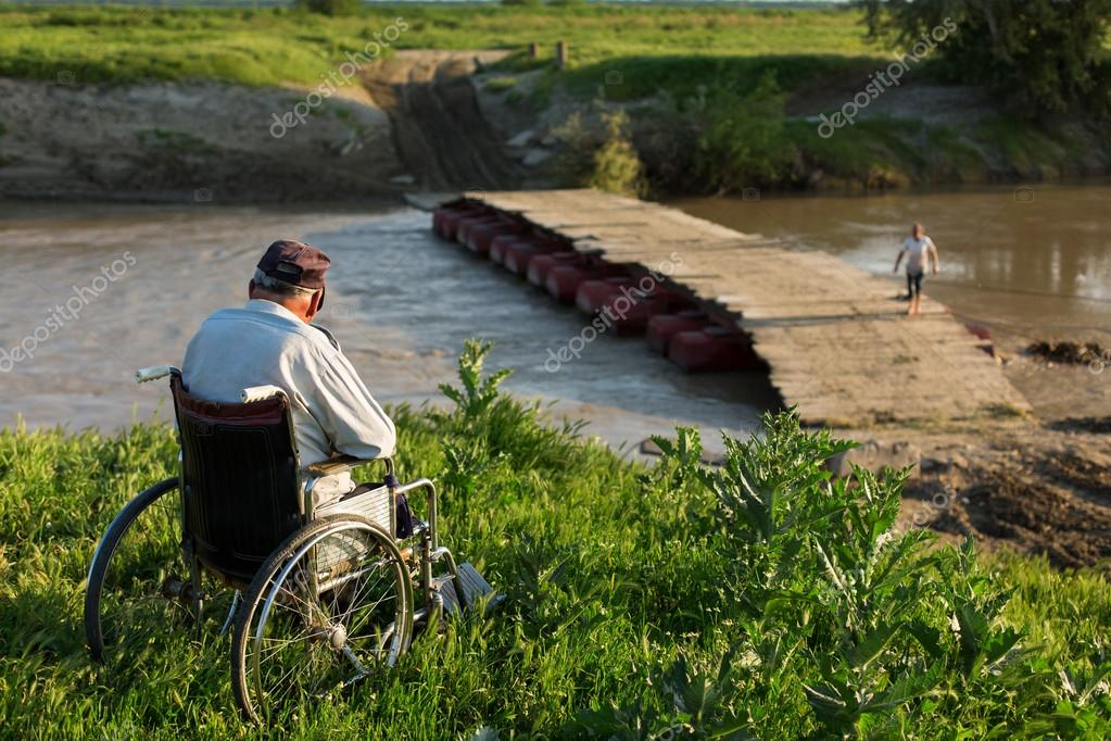 Retired person in a wheelchair admiring bridge over river