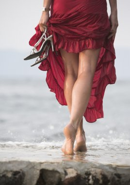 Sexy red dressed woman walks on wet stone next to sea