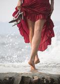 Sexy žena v červených šatech, kroky na mokré skále u moře