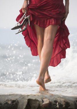 Sexy woman in red dress, steps on wet rock, next to sea