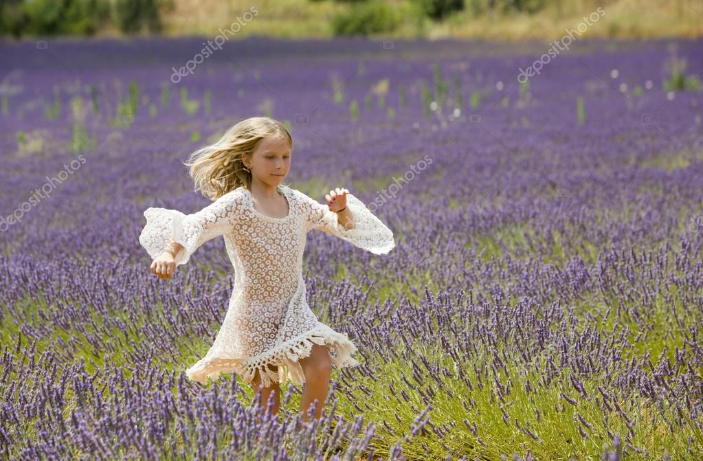 Young girl runs and jumps in a purple field of lavender