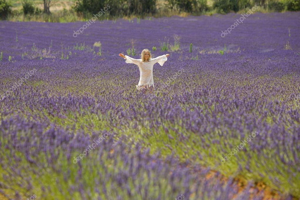 Beautiful little girl runs and jumps in the middle of a field of lavender