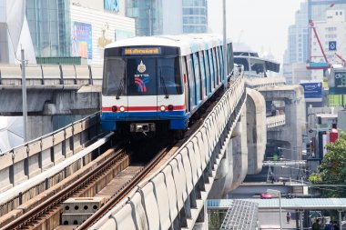 BTS Skytrain passes by on elevated rails above Sukhumvit Road in Bangkok, Thailand.