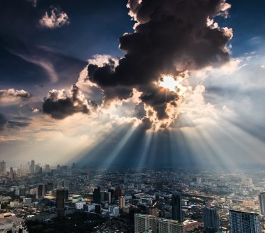 Rays of light shining through dark clouds city