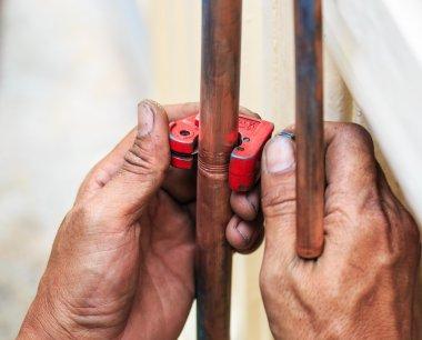 Repairman cut the copper pipe