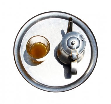 A kettle with a tea glass on a tray