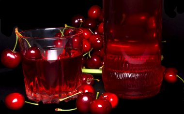 Glass with cherry isolated on a black background.