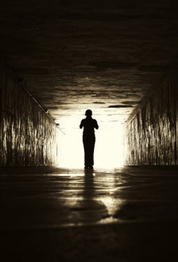 Silhouette of woman in a tunnel.