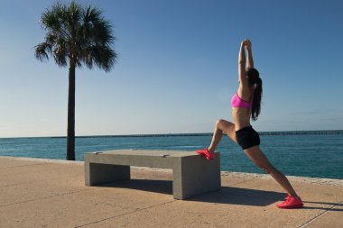 Fit woman stretching along the water
