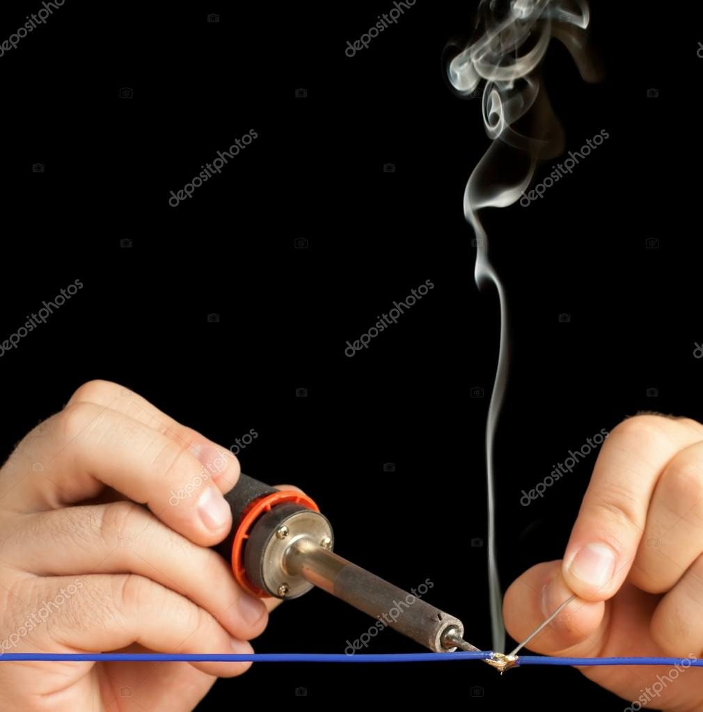 Technician soldering two wires together on a black background ...