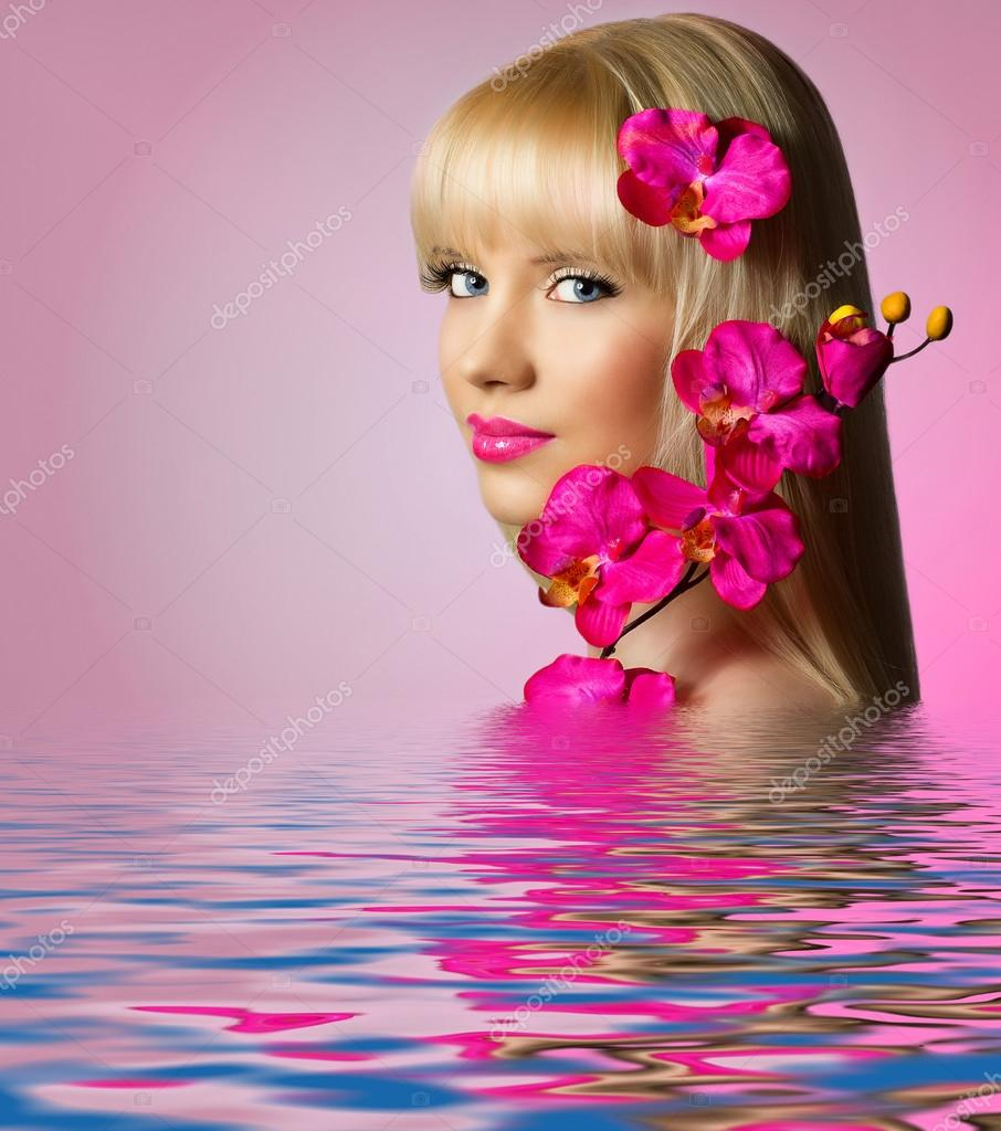 Beautiful woman with orchid flowers in water stock photo beautiful blonde woman with orchid flowers in water photo by dmitrigromov dhlflorist Gallery