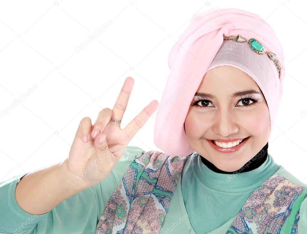 Happy young woman in head scarf making a peace sign