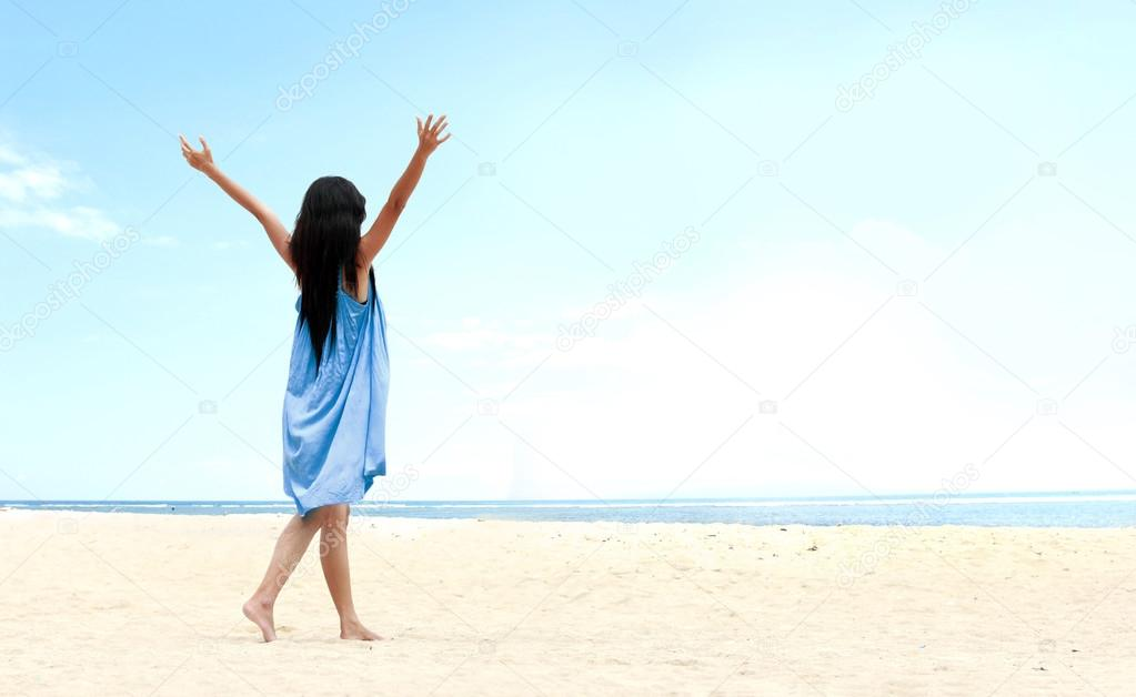 Girl at the beach raised her hands up