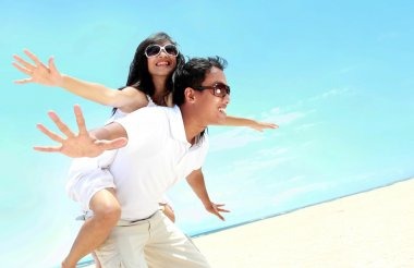 Happy smiling couple piggyback together with arms outstretched
