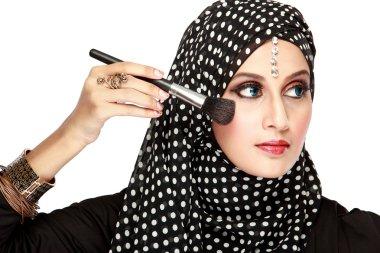 woman in scarf applying blush on