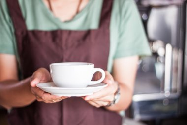 Barista serving freshly brewed coffee