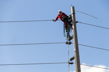 Electricians working on a pylon of the public power line