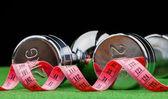 Fotografie fitness činky a měřicí pásky