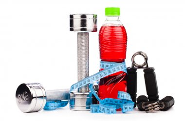 Fitness equipment with fruits and bottle of energy drink isola