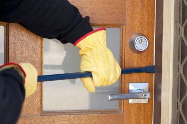 Burglar breaking in house with crowbar at door