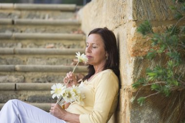 Beautiful mature woman in love with flower