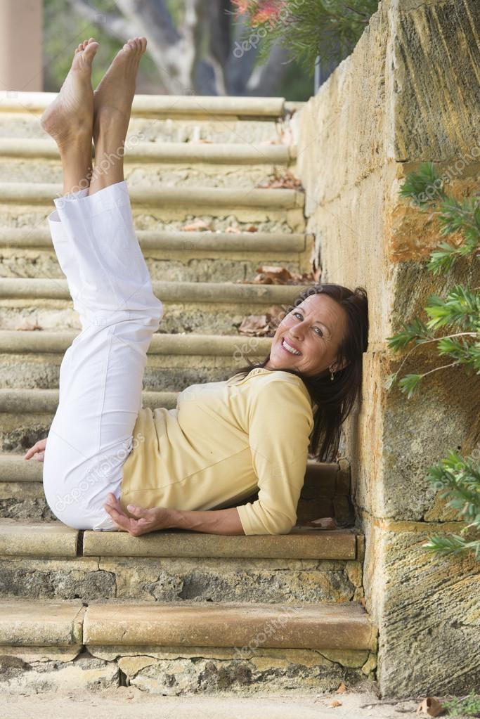 Fit healthy mature woman legs up outdoor