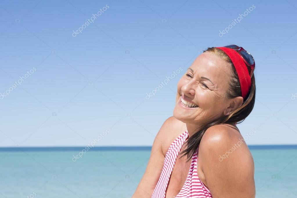 Happy attractive mature woman ocean holiday