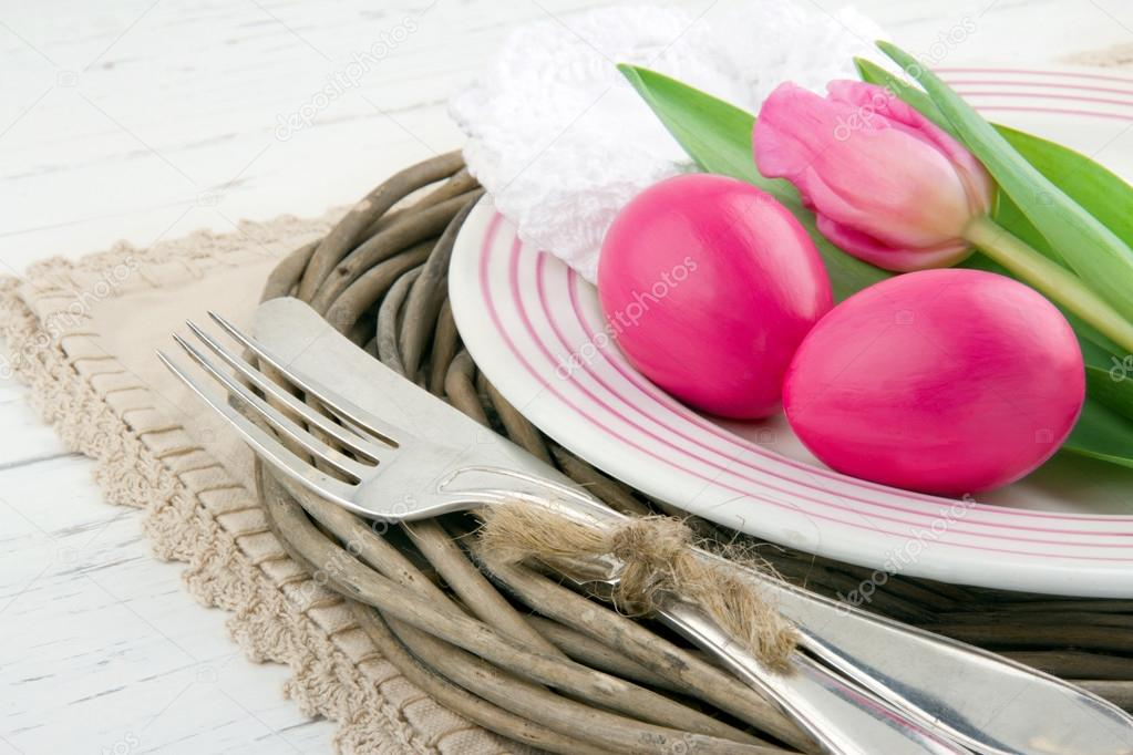Easter dinner setting with two pink eggs and tulip, rustic white wooden background