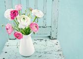 Fotografie bílé a růžové květy na světle modré křeslo
