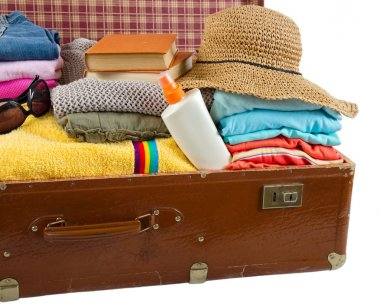 Old vintage suitcase packed with clothes and vacation accessorie
