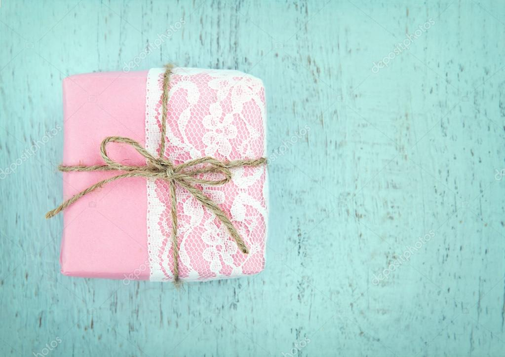 White lace and a simple bow on pink gift box