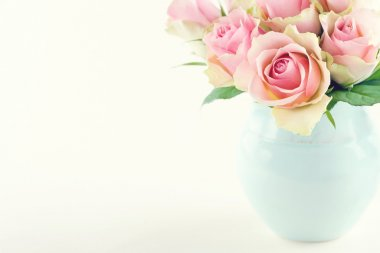 Pink roses in a light blue vase