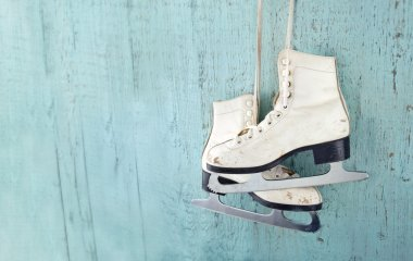 Women's ice skates hanging on blue wooden background