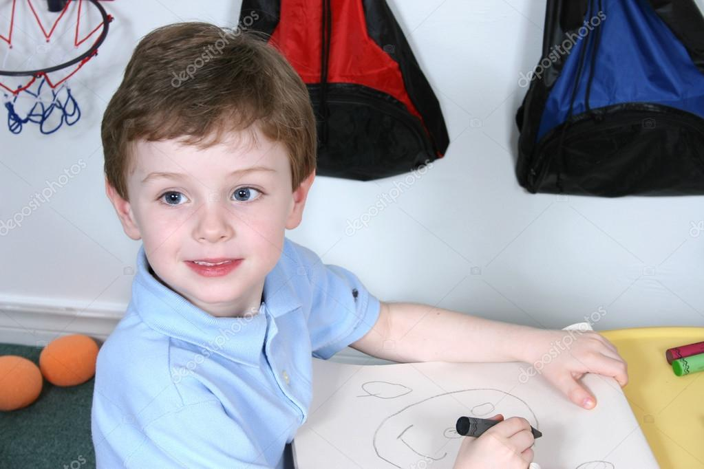 Adorable Four Year Old Boy With Big Blue Eyes Coloring At Presc