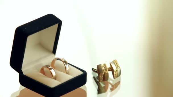 Rings in the box and cufflinks are on a glass table