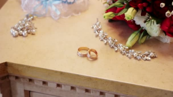 Svatební kytice a zlaté prsteny na stůl