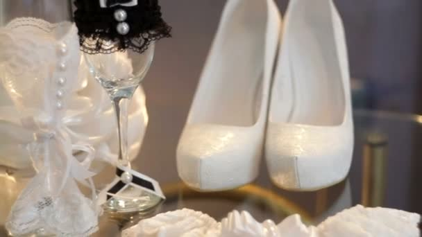 White bridal shoes and wedding accessories on the table