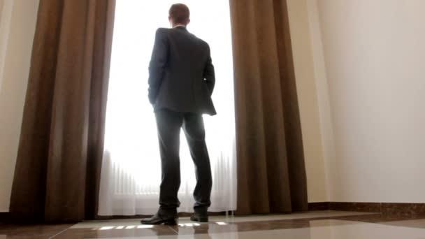 elegantní muž v černém obleku, při pohledu z okna