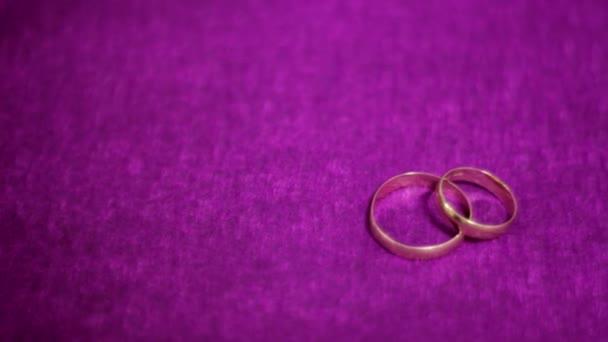 két gyönyörű esküvői gyűrű egy sötét lila háttér