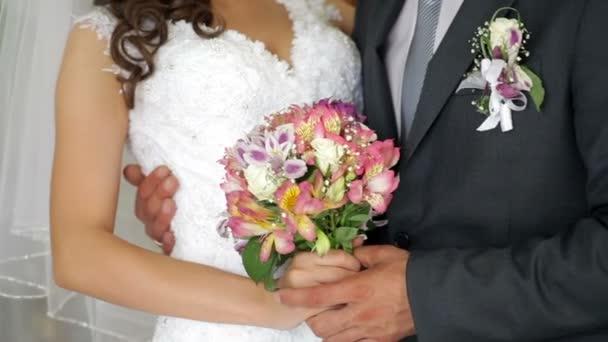 nevěsta a ženich drží svatební kytice
