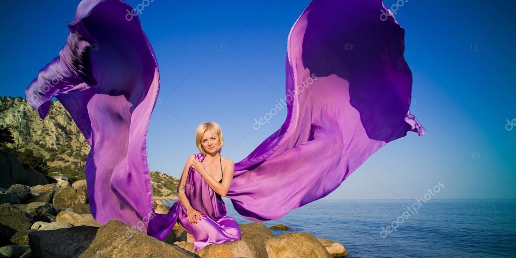 Beautiful girl sitting on a rock near the water