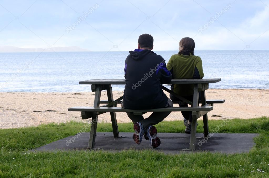Young couple seat on opposite sides of park bench.