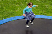 Photo Young girl jumps on trampoline in home back yard.