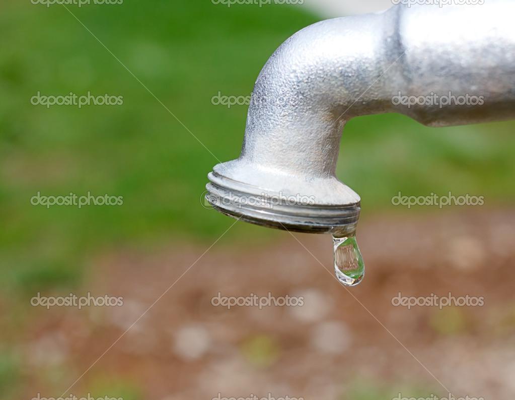 Water drop falling from metal gray tap